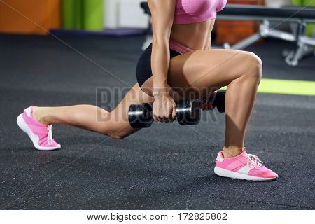 Beautiful sportive woman training with dumbbell in gym