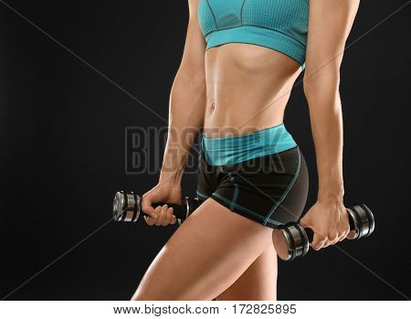 Young athletic woman with dumbbells on black background, closeup