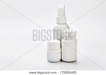 White plastic containers for pills. Little spray bottle. Dose of vitamins for month.