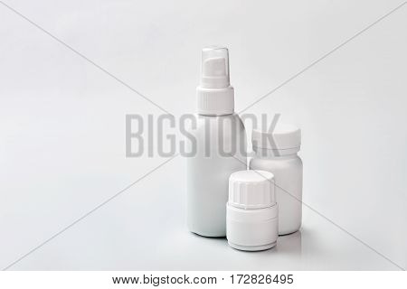 White containers with medicine. Small spray bottle.