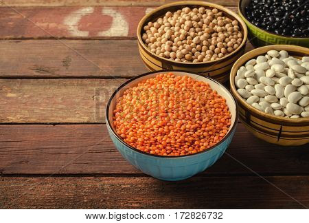 Assorted beans in bowls with red lentil, chick-pea and kidney bean on wooden background. Horizontal, toned