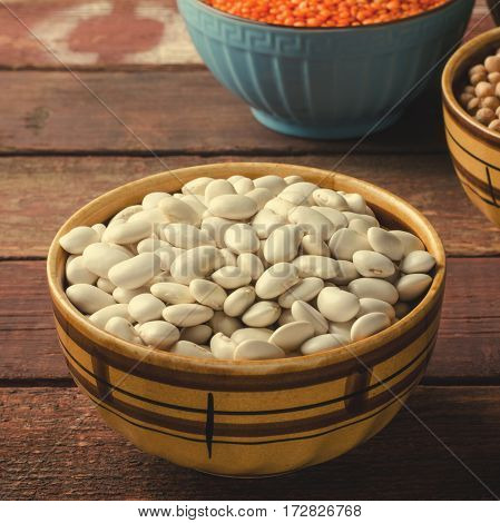 Assorted beans in bowls with red lentil, chick-pea and kidney bean on wooden background. Square, toned
