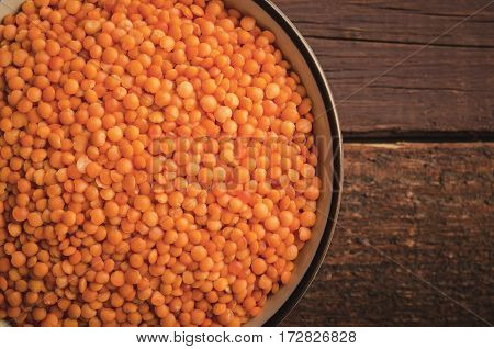 Red lentil in bowl on wooden background. Horizontal, toned, top view, copy space