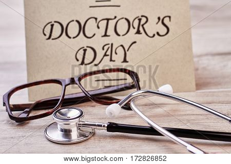 Stethoscope and brown frame glasses. Greeting card on Doctor's Day.