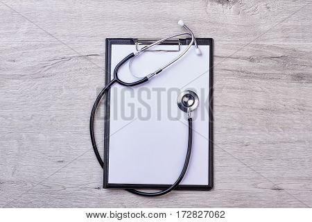 Clipboard with stethoscope. Medical equipment and paper sheet.