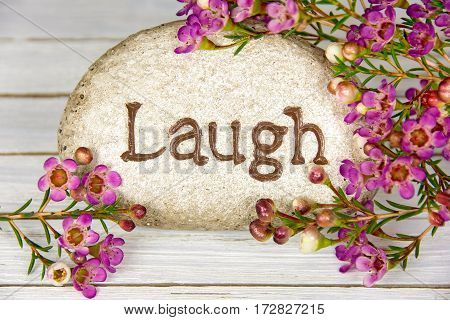 word laugh etched in stone with pink flowers on whitewashed wood