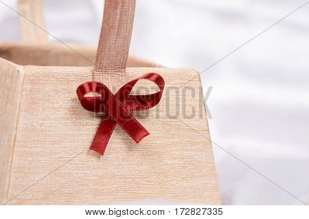 Paper Basket With Red Bow For Flower Arrangements On White Satin