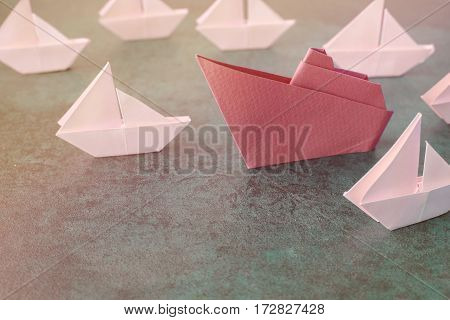 Origami paper ship with small sailboats female woman leadership business concept toning