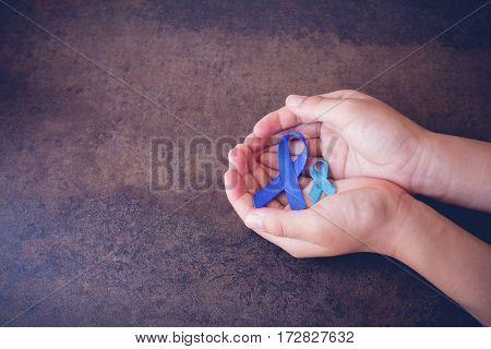 hands holding blue ribbons toning dark background