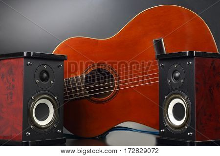 two stereo audio speakers and classical acoustic guitar