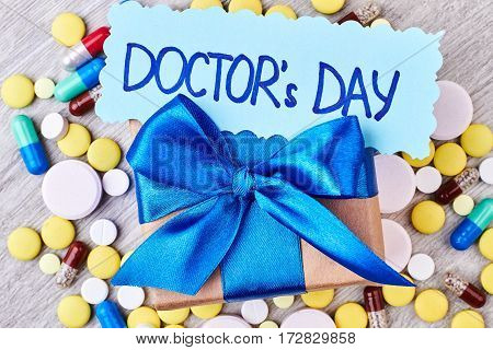 Pills, capsules, box with bow. Creative design for Doctor's Day.