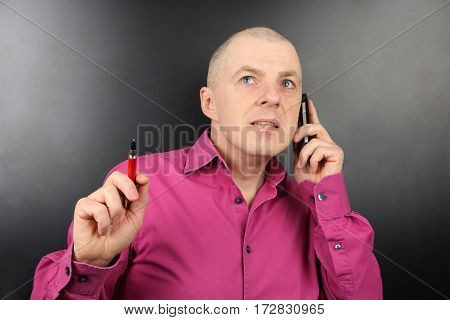 business man in a pink shirt with a pen in hand talking on a cell phone