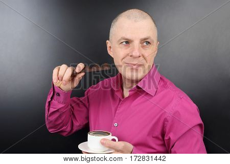 happiest man in the pink shirt with chocolate and a Cup of coffee in hand