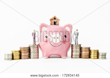 Small house and piggy savings with stack of coins money on white background. Savings for home concept.