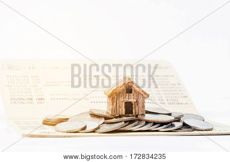 Miniature house stand on the stack of coins on book bank background with light. Financial for house concept.
