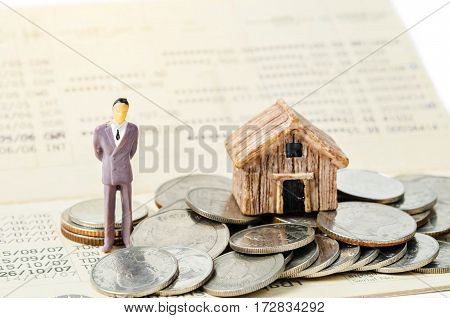 Miniature businessman stand on the heap coins on book bank background with light. Financial concept.