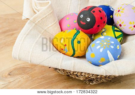 Colorful easter eggs in basket on wooden background.