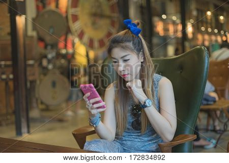woman sitting thinking shopping online by using cellphone in restaurant day time
