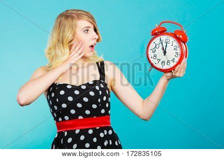 Management time concept. Blonde emotional girl shocked expression wearing dotted dress with alarm clock on blue.