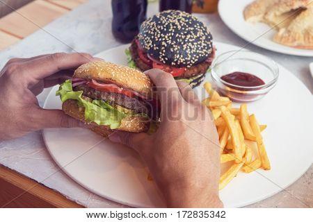 Man eating burgers at table, pov view