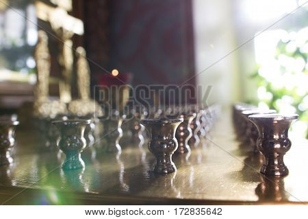 Inside Christian Church - close up view of candle holder in orthodox church at sunny day, horizontal