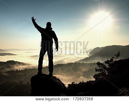 Happy Man With Raised Arms Gesture Triumph  On Exposed Cliff. Satisfy Hiker