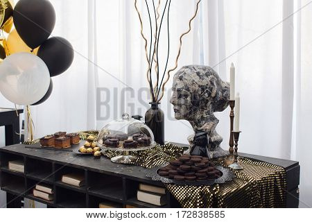 Nice interior in the restaurant with yellow and black balloons, woman's bust and white curtains