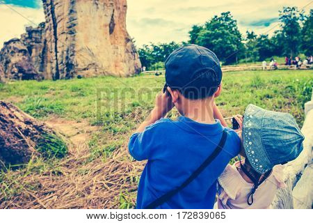 Back view of asian children taking photos by camera at national park . Family relaxing outdoors with bright sunlight on summer day travel on vacation. Child in nature. Cross process and vintage tone.