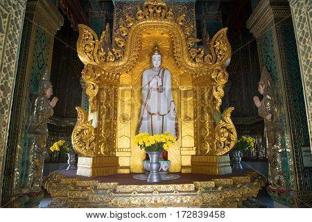 AMARAPURA, MYANMAR - DECEMBER 20, 2016: The sculpture of standing Buddha in the interior of the stupa Mahar Gandar Yone monastery