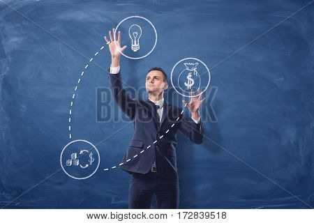 Businessman on blue chalkboard background manipulating white see-through icons that are connected with dash lines. Business and success. Profitable ideas. Monetization.