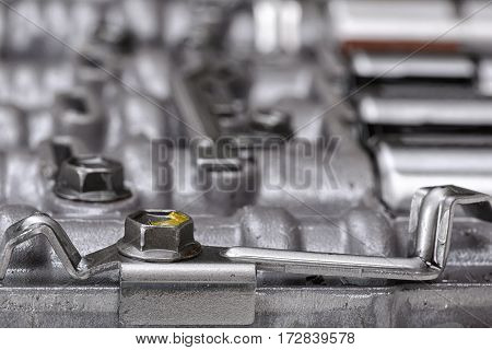 Mechanical parts focused on metal screws holding metal plates. Engineering. Building and repair. Tools and spares.