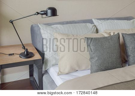 Gray And Brown Pillows On The Bed With Brown Wall And Foldable Reading Lamp
