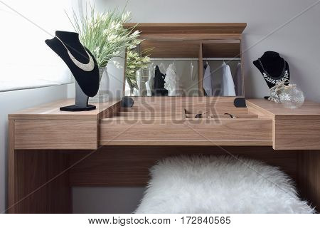 Beautiful Necklaces On Wooden Dressing Table And The White Woolen Stool