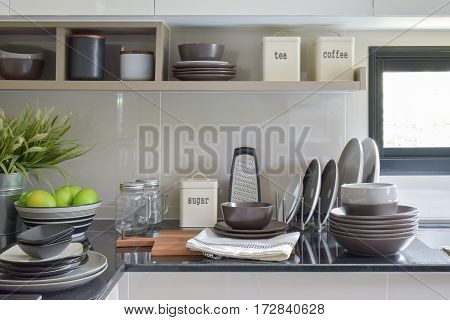 Ceramic Dishes And Bowls On The Counter And Shelf In The Modern Kitchen