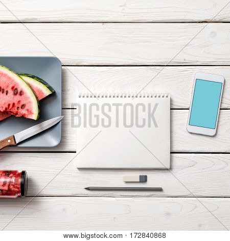 Paper notebook with template of smartphone, knife and slices of watermelone. Clipping path.