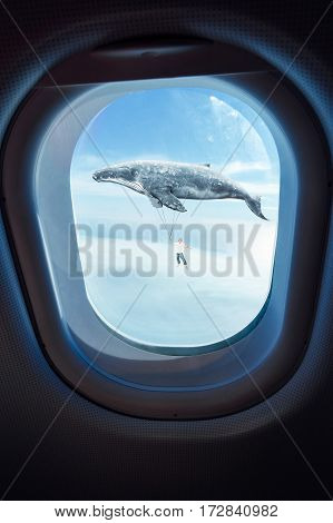 Whale floats in the air above the clouds carrying a young guy seen through window of an aircraft dreams and travel concept .