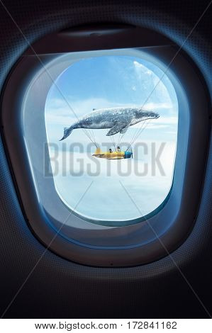 Whale floats in the air above the clouds carrying children in a yellow airplaneseen through window of an aircraft dreams and travel concept .