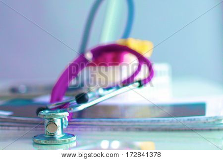 A medical stethoscope near a laptop on table, on white.
