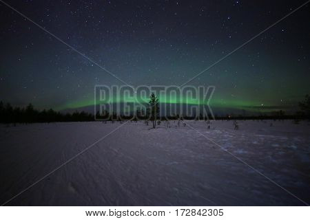 Spectacular northern lights (aurora borealis) over a snowy winter landscape in Finnish Lapland