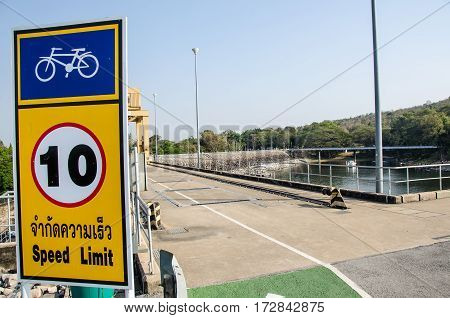 Bicycle sign on a post signaling the speed of 10 km per hour in the dam way.