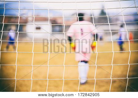 Goalkeeper behind a football goal net poster