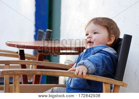 One Year boy sits in director chair in a public cafe in park