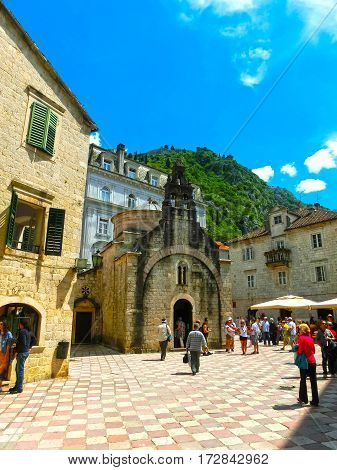 Kotor, Montenegro - May 07, 2014: St. People walking near Luke's Church on St. Luke's square surrounded by traditional stone houses at Kotor's Old Town, Montenegro on May 07, 2014.