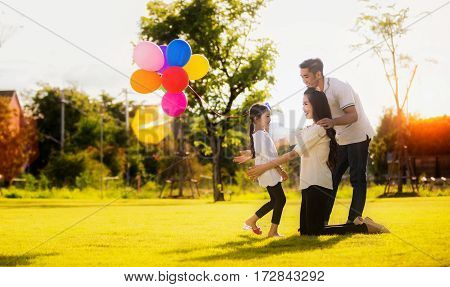 Daughter running to mother and father She enjoyed the play balloons