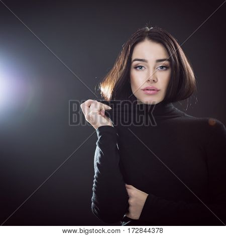 Beautiful girl posing over black background. Young pretty woman in studio.