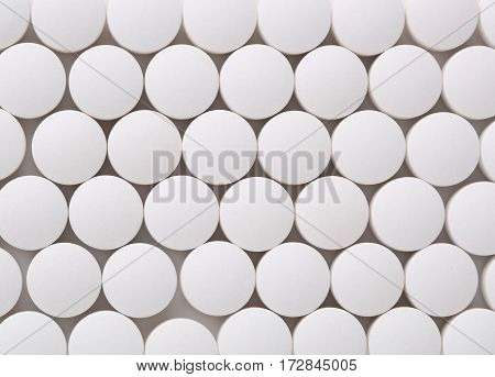 Top view of round white pills closeup sit on a table.