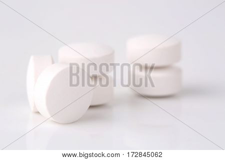 Round white pills closeup sit on a table.