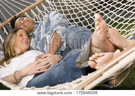 Romantic couple outdoors relaxing on a hammock.