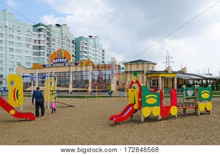 GOMEL BELARUS - APRIL 14 2016: Man with child are on modern children's playground with bright colored constructions in sleeping district on street Khatayevich Gomel Belarus