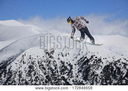 Snowboard rider jumping on mountains. Extreme snowboard sport.